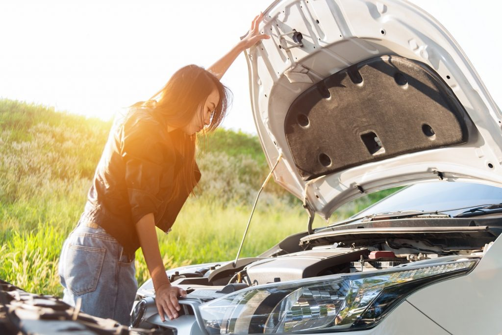 Female checking her car engine