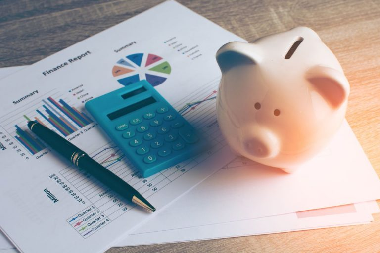 calculator and piggy bank with report sheets