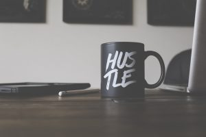 "black mug with the word ""hustle"" written on it"
